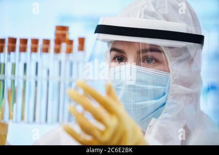Female scientist in clean suit examining test tubes