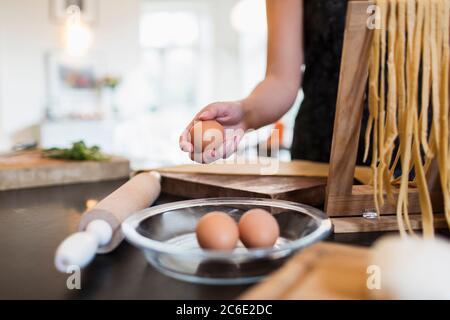 Woman making fresh homemade pasta in kitchen - Stock Photo