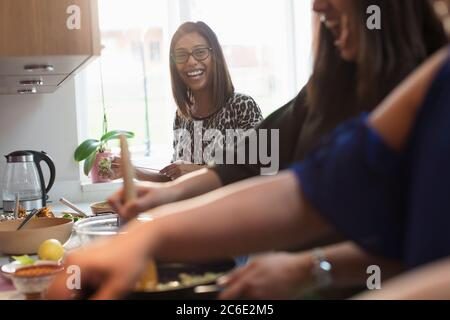 Happy Indian women cooking food in kitchen - Stock Photo
