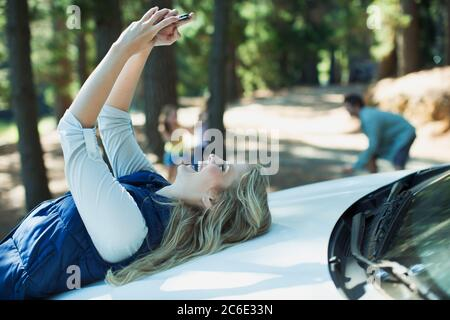 Enthusiastic woman taking self-portrait on hood of car in woods - Stock Photo
