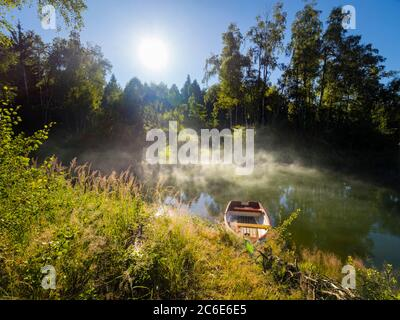 Stunning morning sunlight in Green early Summer forest wooden boat and evaporating vapor above calm lake river water surface Mrzla vodica Croatia
