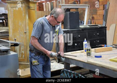 middle aged Caucasian balding Man rebuilding parts to repurposed older furniture in custom shop with hand tools to save and reuse in a home - Stock Photo