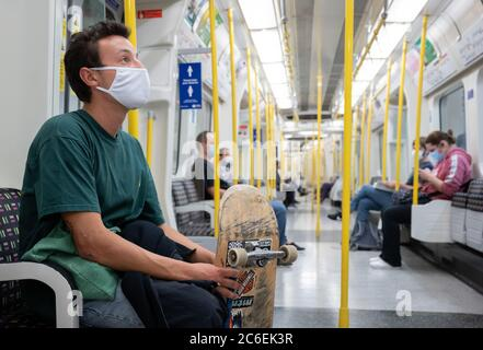 Commuters wearing face masks on the London Underground .  Circle Line.  July 6, 2020. London, UK.      CONSENT FORM SIGNED FOR MAN WITH SKATEBOARD FOR - Stock Photo
