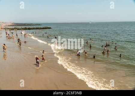 Thousands of beachgoers generally observe social distancing as they try to beat the heat and humidity at Coney Island in Brooklyn in New York on the long Independence Day weekend, Sunday, July 5, 2019.  (© Richard B. Levine) - Stock Photo