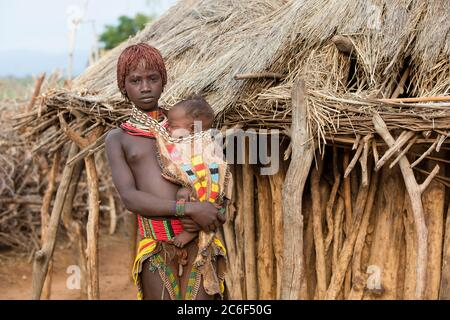 Young black girl with baby of the Hamar / Hamer tribe in village in the Omo River valley, Debub Omo Zone, Southern Ethiopia, Africa - Stock Photo