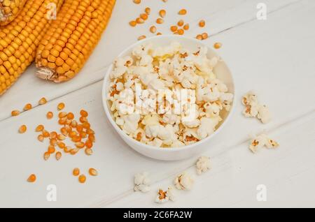 Popcorn in a bowl on a white wooden background with ears of corn