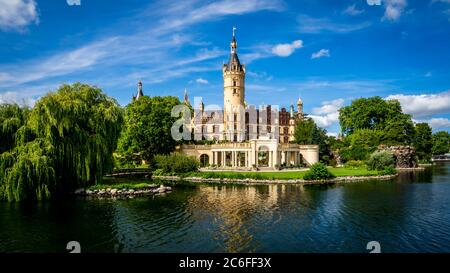 lake view of the popular schwerin castle the seat of the regional government office in mecklenburg western pomerania in front of blue sky with clouds - Stock Photo
