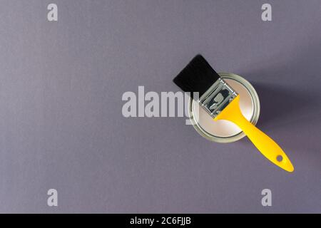 Can of white paint with a yellow brush on gray background, painting, top view
