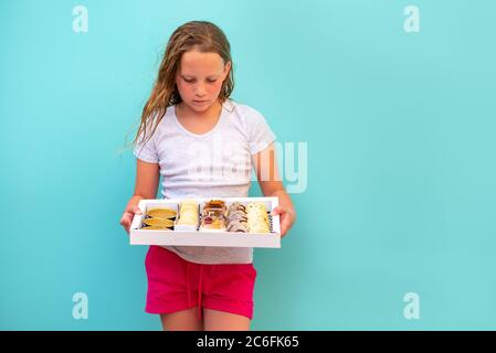 Cute teenage girl freckles woman holding box with dessert chocolate and vanilla mousse decorated with sweet cream, cookies and candy in a glass jar, fruit sushi, alfajores, macaroons and creme brulee. - Stock Photo