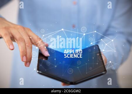Businessman holding a foldable smartphone with APPLIED SCIENCE inscription, new technology concept