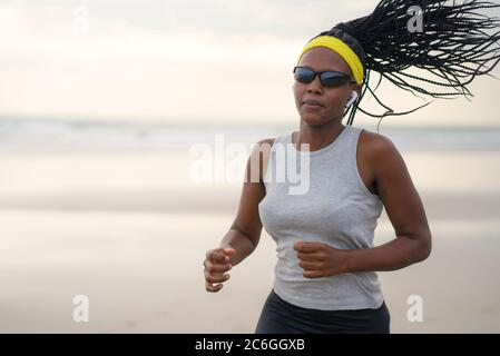 african American woman running on the beach - young attractive and athletic black girl training outdoors doing jogging workout at the sea in fitness a - Stock Photo