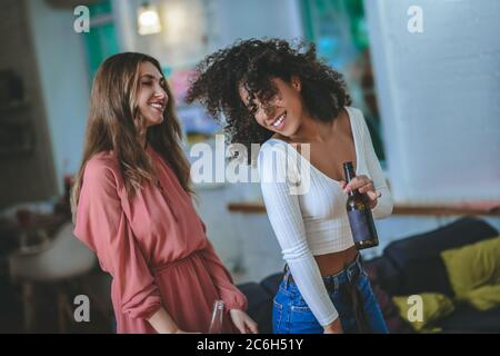 Two young adult girlfriends with bottles of drink dancing in room - Stock Photo