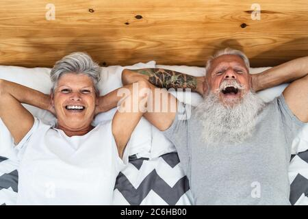 Happy senior couple in bed - Hipster mature people having funny bed time together - Elderly lifestyle and love relationship concept Stock Photo