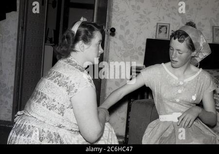 1950s, historical, ...a telling off!....'now listen to me young lady'....at home, a mother having a stern word with her teenage daughter, England, UK. In this era, discipline was important in households and parents had strict rules for possible wayward youngsters. - Stock Photo