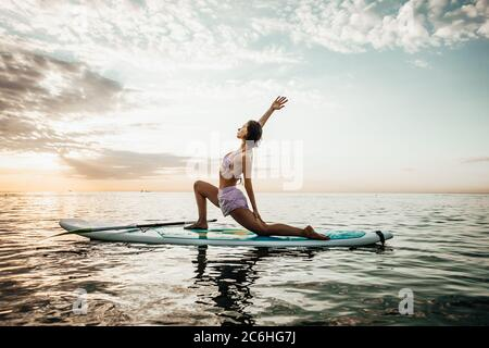 Young woman doing YOGA on a SUP board in the lake at sunrise Stock Photo