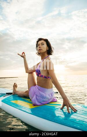 Young woman doing YOGA on a SUP board in the lake at sunrise - Stock Photo