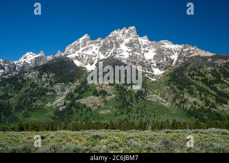 Beautiful mountain peaks of hte Tetons in Grand Teton National Park in Wyoming near Jackson Hole. Clear sunny day with blue sky - Stock Photo
