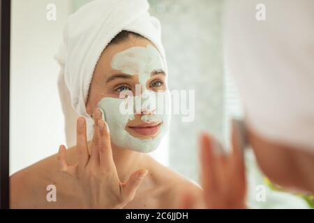 Woman applying face pack while looking in the mirror