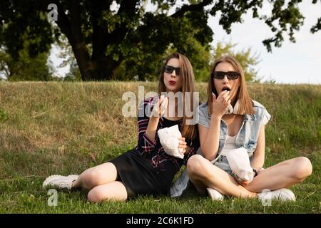 Two girls are sitting in the park right on the grass and eating popcorn. Girlfriends watch a movie in an outdoor movie theater.