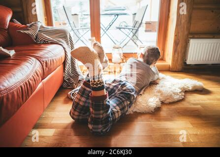 Boy lying on floor on sheepskin and looking in window, dressed in cozy home pajama and warm socks