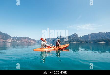 Father and son together paddling in kayak on the Cheow Lan lake in Thailand. Vacation with kids concept image. - Stock Photo