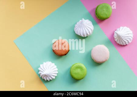 Flat lay of french macarons and meringues on colorful background. Top view.white meringues,Many sweet zephyrs. Trendy dessert image. Bakery products