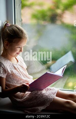 Cute little girl reading book at home, at windowsill - Stock Photo