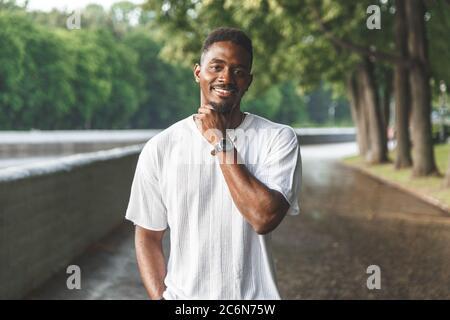 Young man smiling at camera in a park. Horizontally framed shot. - Stock Photo