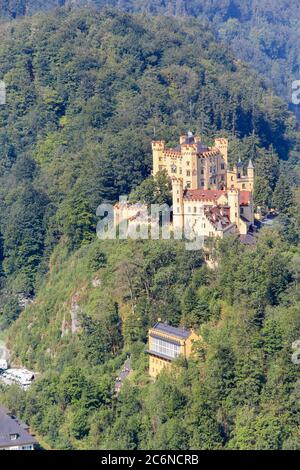 Schwangau, Germany - August 12, 2015: Hohenschwangau Castle  surrounded by forest in summer time. It is a 19th-century castle in southern Germany. It - Stock Photo