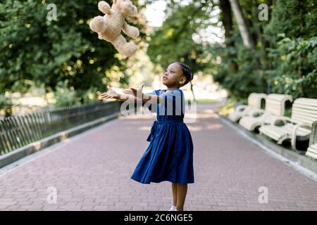 Portrait of happy little African girl child in green city park throwing up teddy bear toy, flying in the air. Smiling dark skinned kid girl in blue - Stock Photo