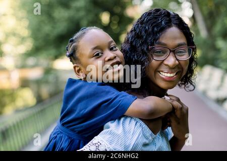 happy dark skinned African mother holding her child in a park. Smiling cheerful young mother carrying her cute little daughter on piggyback and having