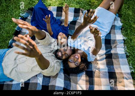 Happy African family resting and having fun on picnic in city park, enjoying and lying on checkered plaid in meadow, on green grass. Parents and child Stock Photo