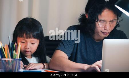 Father using laptop make overtime and daughter doing school homework on ofiice work table in home at night time