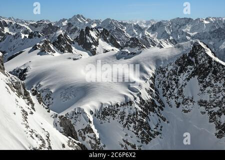 A blanket of fresh snow covers the Grassengrat and the Firnalpeligletscher in winter. - Stock Photo
