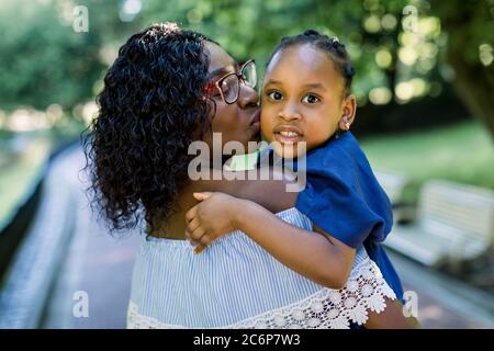 Close up portrait of little cute smiling African child girl in blue dress, looking at camera, while hugging pretty mother, kissing her in the cheek