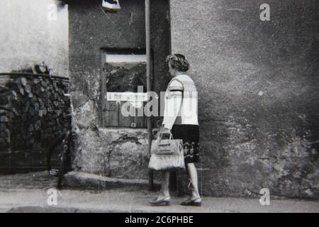 Fine 70s vintage black and white lifestyle photography of a woman walking around a small town in Germany.