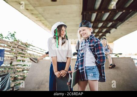 Two kids girls skateboarders talking on background skate park and friends. Girlfriends on ramp with skateboard standing. Group of children at
