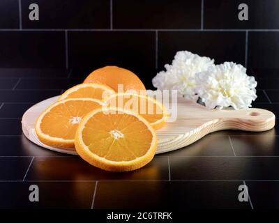 Fresh orange citrus fruit sliced and arranged on a round wooden cutting board with two white carnations behind it on a black subway tile surface.  Foo - Stock Photo