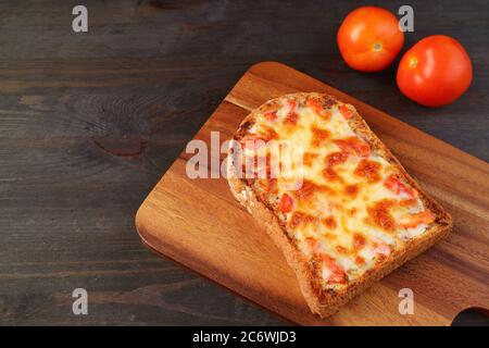 Fresh baked homemade pizza toast with pair of fresh tomatoes on wooden table