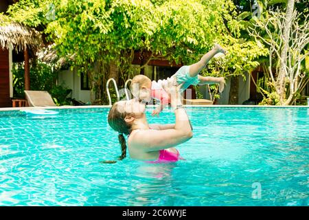 Mom with a happy small child of eight months having fun and swimming in the pool. Young woman kissing her baby. - Stock Photo