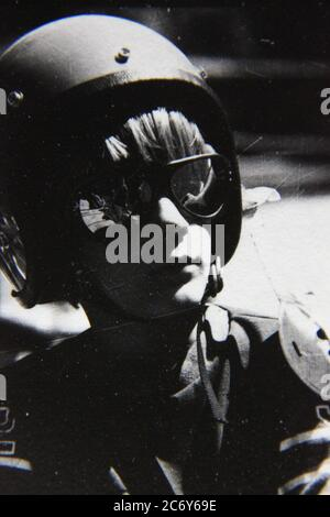 Fine 70s vintage black and white lifestyle photography of a boy wearing a racing helmet and looking good. - Stock Photo