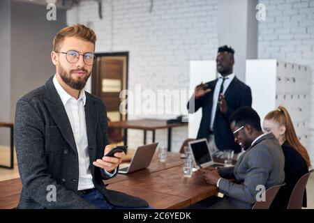 Handsome young man in tuxedo and eyeglasses using smartphone in workplace while his business colleagues having conversation in background