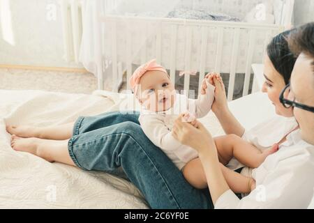 Happy young father, mother and cute baby boy lying on light bed.