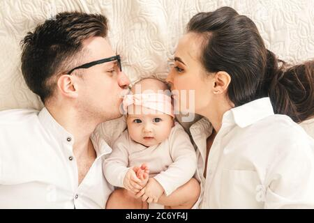 Happy young father, mother and cute baby boy lying on light bed. Mother and father kiss baby.