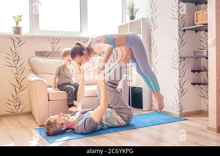 A sports family is engaged in fitness and yoga, baby boy looking, at home. Stay home in quarantine.