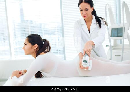 Close up shot of therapist beautician makes LPG massage treatment to young woman in white transparent suit, lying at beauty SPA clinic. Focus on hands