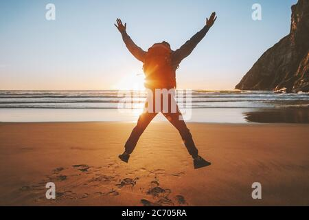 Man jumping on beach travel healthy lifestyle active vacations outdoor adventure success happy emotions traveler enjoying sunset ocean landscape - Stock Photo