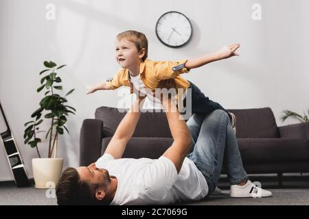 father lying in floor and holding adorabe son imitating flying with outstretched hands