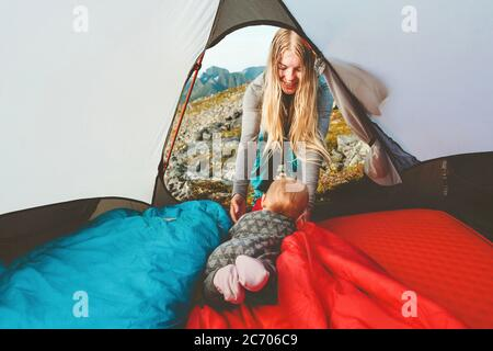 Baby and mother in camping tent family travel vacation adventure lifestyle child hiking with parents outdoor gear equipment