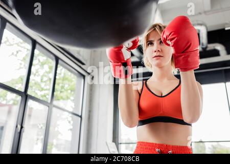 selective focus of young sportswoman in boxing gloves looking at punching bag - Stock Photo